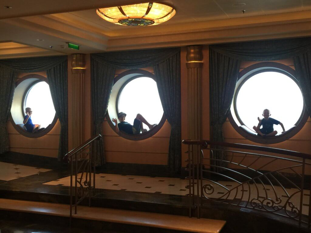 18 Top Secret Disney Fantasy Tips and Tactics  featured by top US family travel blog, Travel with a Plan: image of Boys sitting in porthole on Disney Cruise