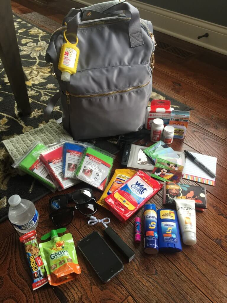 Disney World Essentials featured by top US family travel blog, Travel wit a Plan: image of a backpack with Disney park bag supplies laid out