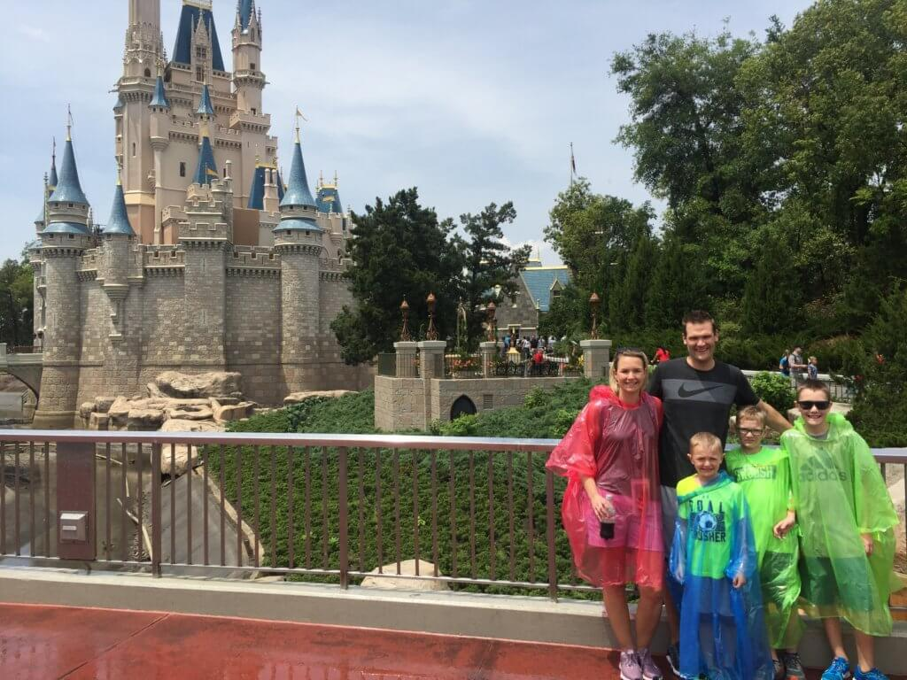 Disney World Essentials featured by top US family travel blog, Travel wit a Plan: image of a family wearing rain ponchos from our Disney park bag