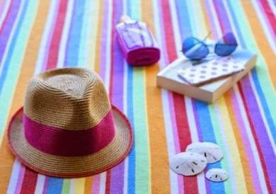 Beach towel with hat, book, and sunglasses